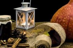 黑暗的秋天静物画用南瓜、蜡烛和灯,有yello的 库存照片
