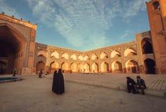 黑暗的穆斯林的妇女穿戴走通过有庭院的一个历史波斯清真寺 免版税库存图片