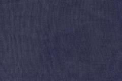 黑暗的紫罗兰色颜色成颗粒状的牛仔裤纹理  库存图片