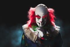 黑暗的背景的可怕小丑 库存图片