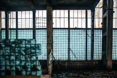 黑暗的蠕动的被放弃的工厂厂房里面与从大块玻璃的残破的被破坏的墙壁 库存图片