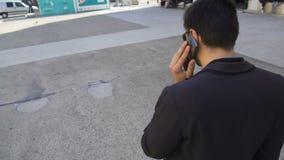 黑暗的衣服的大忙人讲话在电话和走的城市街道,活跃生活 股票视频
