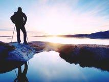 黑暗的运动服的远足者有杆和运动的背包的 在岩石岸的海岸线足迹 单独游人享用 库存照片