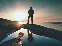 黑暗的运动服的远足者有杆和运动的背包的 在岩石岸的海岸线足迹 单独游人享用 免版税库存图片