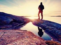黑暗的运动服的远足者有杆和运动的背包的 在岩石岸的海岸线足迹 单独游人享用 图库摄影