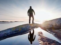 黑暗的运动服的远足者有杆和运动的背包的 在岩石岸的海岸线足迹 单独游人享用 免版税库存照片