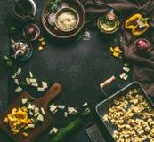 黑暗的食物和烹调与自创素食意大利式饺子的背景框架在黑暗的土气桌上的盘子与菜成份 免版税库存照片