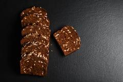 黑暗的黑麦,与向日葵种子的谷物面包在一个黑暗的背景页岩板,健康吃,文本的,集合地方的概念 免版税库存照片