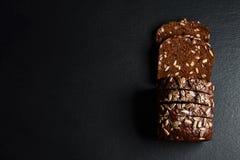 黑暗的黑麦,与向日葵种子的谷物面包在一个黑暗的背景页岩板,健康吃,集合的概念 免版税图库摄影