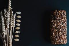 黑暗的黑麦,与向日葵种子的谷物面包, Wonder面包,麦子抽去,在一个黑暗的背景页岩板,概念的南瓜籽  免版税库存照片
