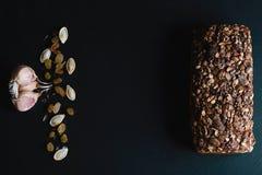 黑暗的黑麦,与向日葵种子的谷物面包, Wonder面包,麦子抽去,南瓜籽,坚果,在一头黑暗的背景页岩公猪的大蒜 免版税库存照片