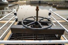 黑有文本的金属钝齿轮控制水闸特写镜头在泰语意思'物产'与在wa的反射 库存图片