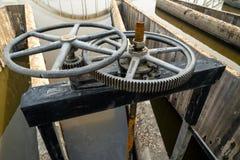 黑有文本的金属钝齿轮控制水闸特写镜头在泰语意思'物产'在一边 免版税库存图片