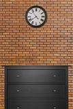 黑木内阁和时钟在有红砖墙壁的空的屋子里 库存图片