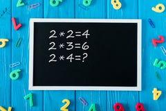黑板和在蓝色木的纸夹顶视图有乘法表五颜六色的数字的 免版税库存照片