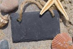 黑板在木头的板岩板与沙子、壳和星鱼 免版税图库摄影