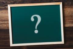 黑板在木桌上的书面问题标记 免版税图库摄影