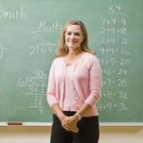 黑板最近的常设教师 免版税库存图片