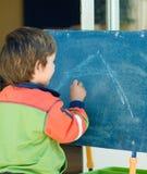 黑板男孩绘画 免版税图库摄影