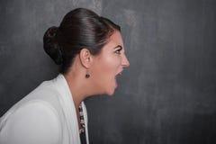 黑板背景的恼怒的叫喊的妇女 侧视图 免版税库存图片