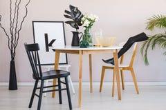 黑椅子在与叶子和花的木桌上在餐厅内部与海报 实际照片 免版税图库摄影