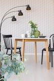 黑椅子在简单的餐厅内部的木桌上与灯和植物 实际照片 库存照片