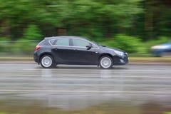 黑汽车在一条湿路驾驶 都市的生活 免版税库存图片