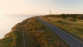 黑汽车沿海峭壁乘坐在夏天在日落 在背景中老灯塔 股票视频