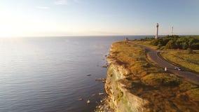 黑汽车沿海峭壁乘坐在夏天在日落 在背景中老灯塔 股票录像