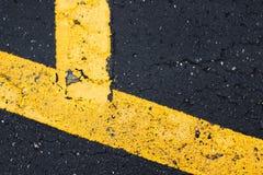 黑沥青表面上的黄色漆线 免版税库存照片