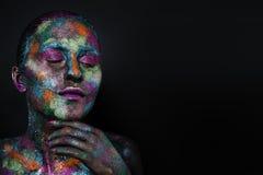 黑油漆和五颜六色的粉末的年轻艺术性的妇女 发光的黑暗的构成 在空间题材的创造性的人体艺术  免版税库存图片