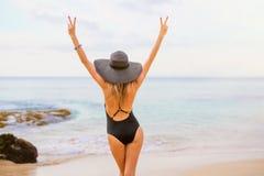 黑泳装和夏天帽子的妇女在海滩 免版税库存图片