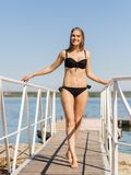 黑泳装的美丽的白肤金发的女孩在水背景 游泳时尚概念 复制空间 库存照片