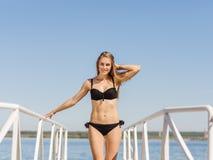 黑泳装的美丽的白肤金发的女孩在水背景 游泳时尚概念 复制空间 库存图片