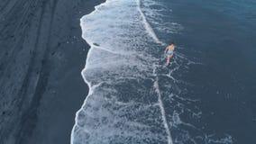 黑海洋海滩的空中英尺长度在日落的在有美丽的女孩的巴厘岛,美妙的看法 股票录像