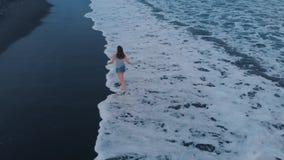黑海洋海滩的空中英尺长度在日落的在有美丽的女孩的巴厘岛,美妙的看法 影视素材