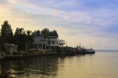 黑海海岸用走沿散步的咖啡馆和人在日落 免版税库存图片