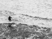 黑海 有一个风帆冲浪委员会的运动员以波浪为背景和海起泡沫 图库摄影
