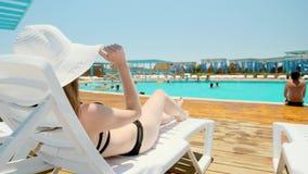 黑游泳衣和一个白色帽子的愉快的女孩在懒人说谎在水池附近外面 他别住一个帽子 一真正 股票视频
