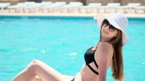 黑游泳衣和一个白色帽子的愉快的女孩坐在室外的水池边缘 在水中移动他的脚 股票视频