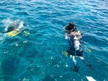 黑潜水的潜水者在度假防水与铝罐漂浮的发光的金属,下潜的衣服到蓝色清楚的海水,海里 库存照片