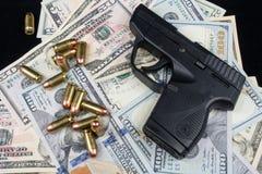 黑火器和子弹特写镜头在堆美国货币反对黑背景 库存图片