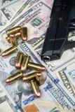 黑火器和子弹特写镜头在堆美国货币反对黑背景 免版税图库摄影