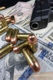 黑火器和子弹特写镜头在堆美国货币反对黑背景 免版税库存照片