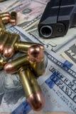 黑火器和子弹特写镜头在堆美国货币反对黑背景 免版税库存图片
