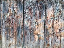 黑灰色老木墙壁,有老削皮,从二垂直的老漫无边际的板的削皮油漆片断的篱芭的纹理  库存照片