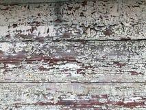 黑灰色老被毁坏的木墙壁,有老破旧的被剥落的油漆片断的篱芭的纹理从水平的破旧r的 免版税库存照片