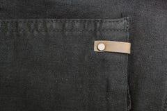 黑牛仔布背景与铜元素和缝的 r 图库摄影