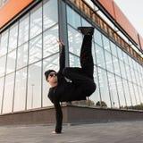 黑牛仔裤的可爱的年轻行家人在一个被编织的帽子的一件衬衣在跳舞在城市的运动鞋的太阳镜 库存图片