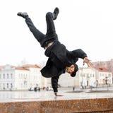 黑牛仔裤的时髦的年轻人舞蹈家在一个盖帽的一件时髦的夹克在太阳镜在街道上的城市做手倒立 免版税图库摄影